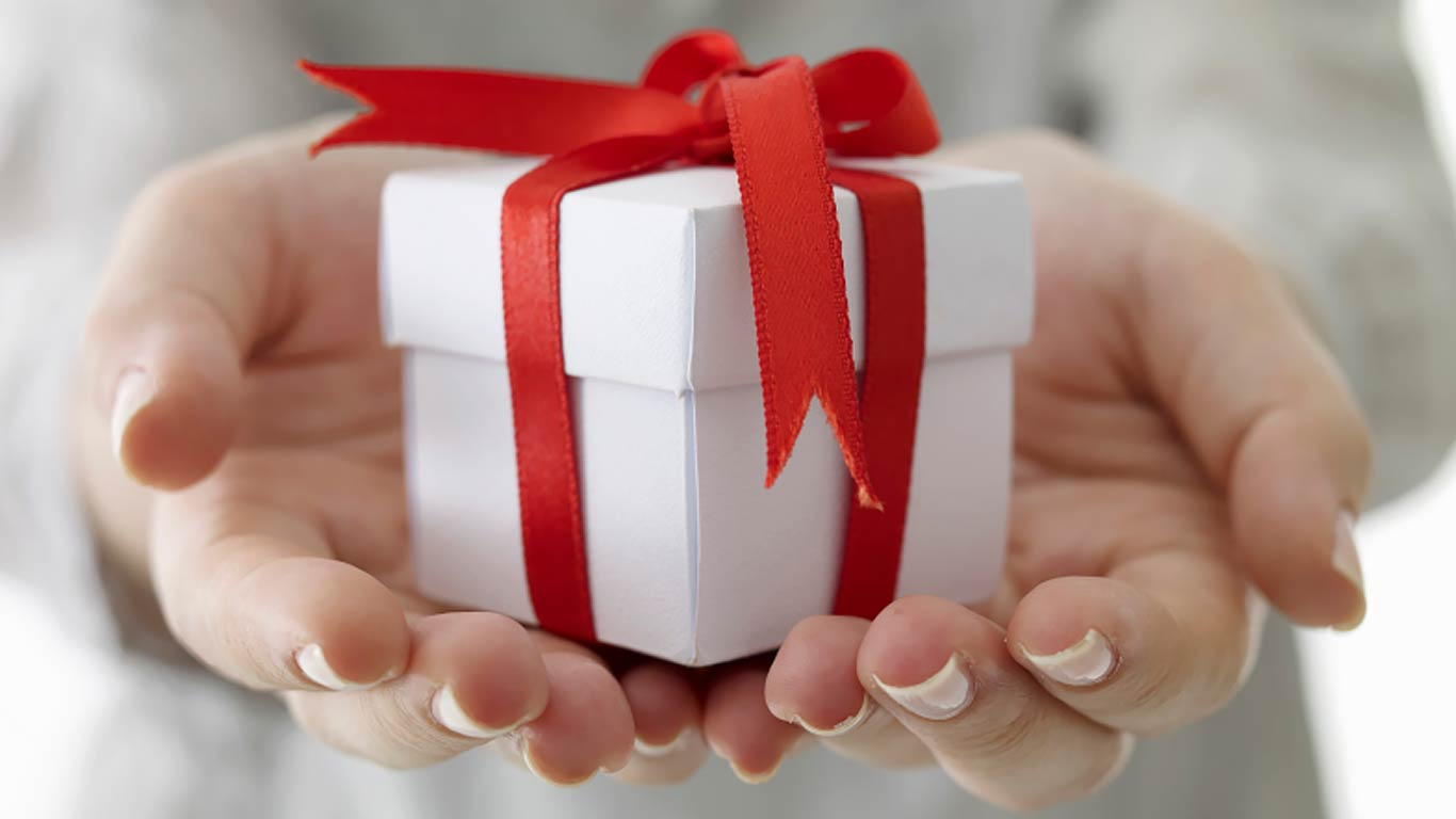 Handing holding a gift box with a red ribbon